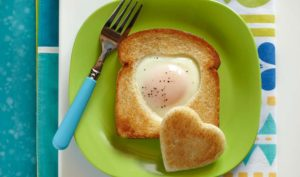 Toast with a heart-shaped cutout filled with fried egg on a green plate next to a fork